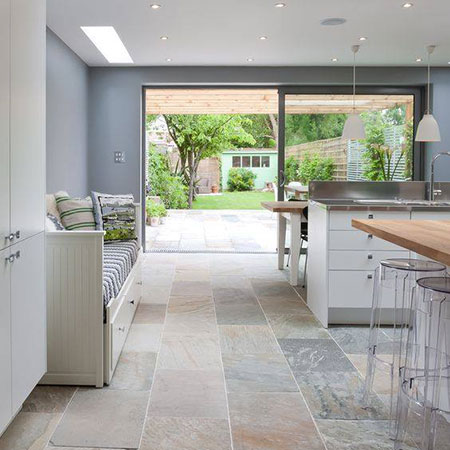 kitchen with tiled floor looking into garden with lawn and shed