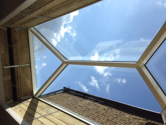 blue sky and white clouds seen through a rooflight