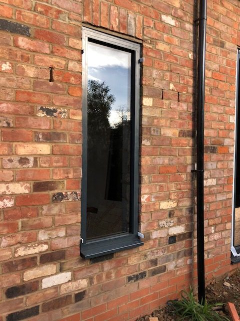 red brick wall with slim window and drainpipe