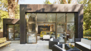 glass and wood house set within trees patio furniture