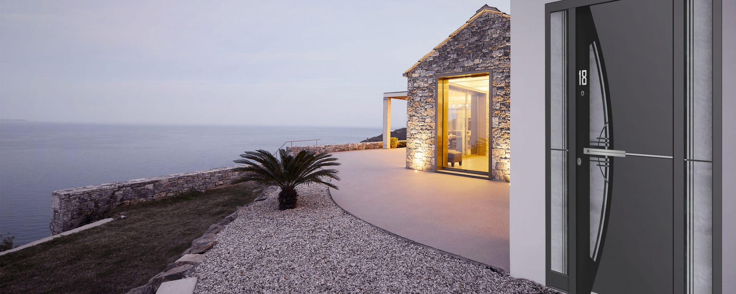 Front door and view of patio area overlooking sea