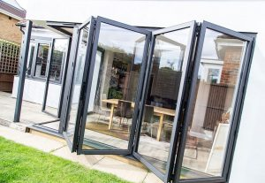 open bi-fold patio doors with dining table and chairs