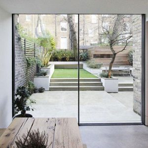 patio area with steps up to lawn and outdoor seating areas and slimline sliding doors