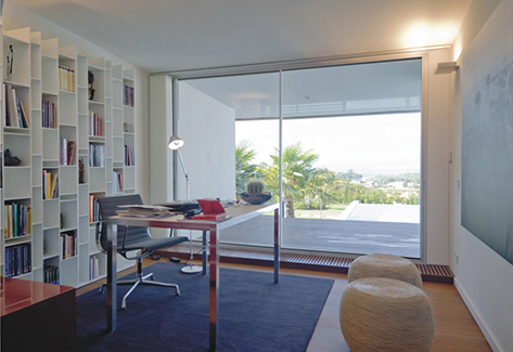 office with desk and chair and shelving with views over patio area with sliding doors