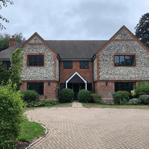 double fronted house with grid windows and stone wall feature