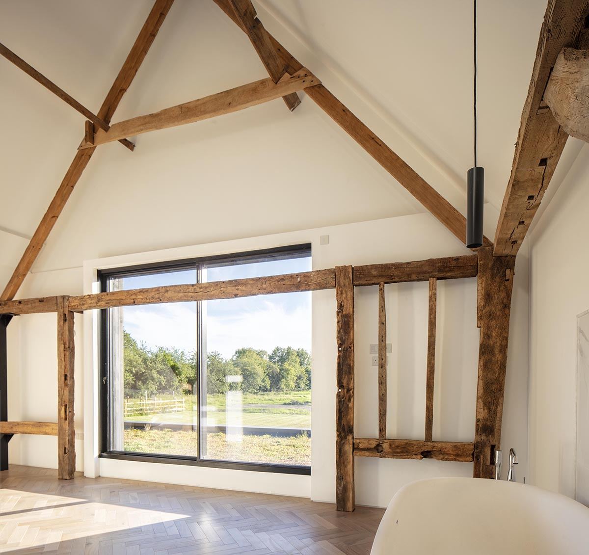white painted room with large window and exposed wooden beams