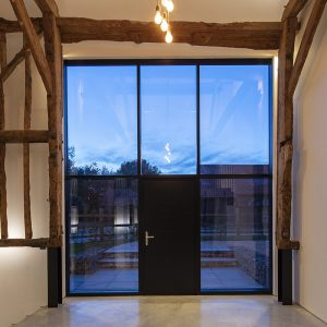 entrance hall with wood beams front door and curtain wall
