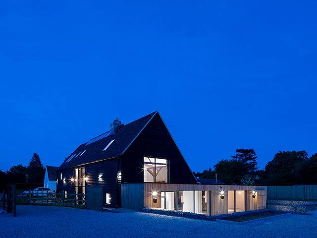 House with lights on against a vivid blue sky