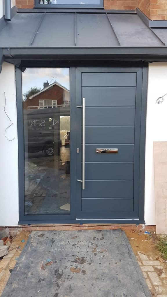 modern front door with long metal handle and glass to the left