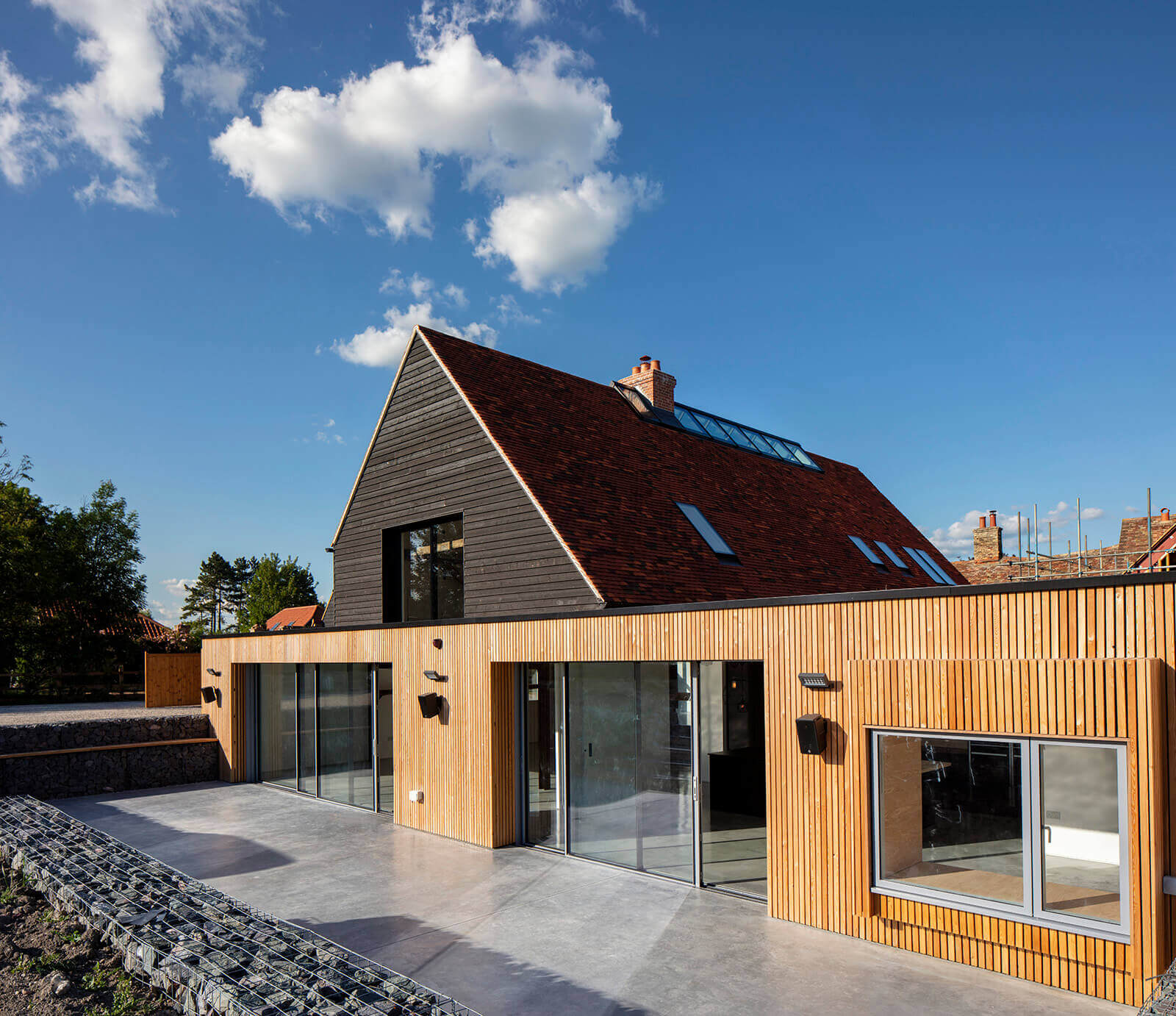 Side aspect of modern house wood panelling and large windows