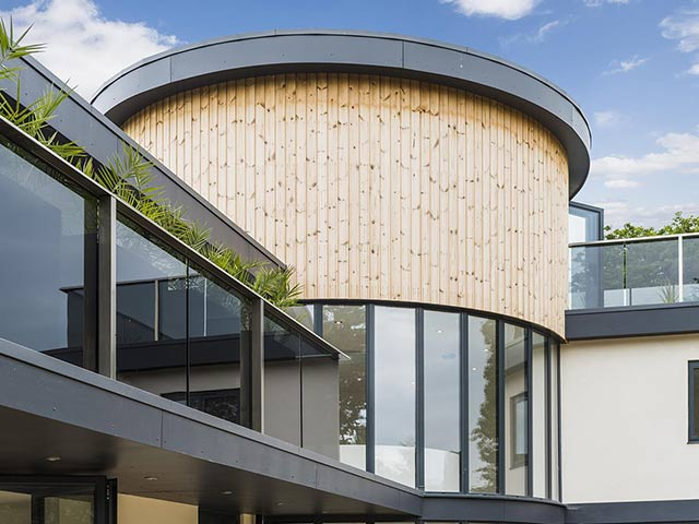Modern house with wood panelled round and glass room