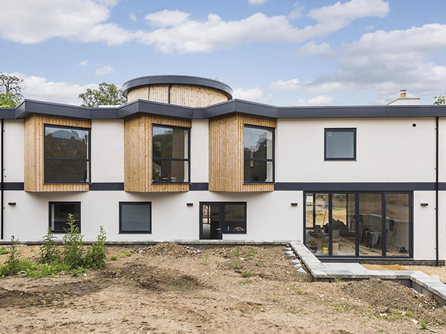 New build white modern house with wood panels and large windows
