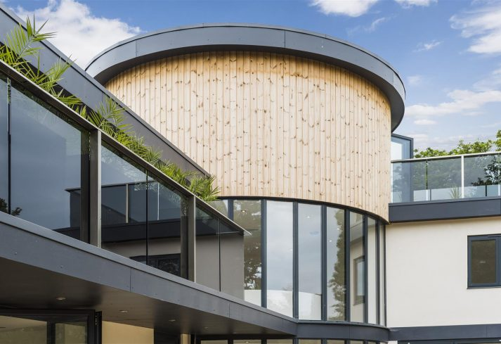 Modern house with wood panelling on round feature tower and glass curtain wall