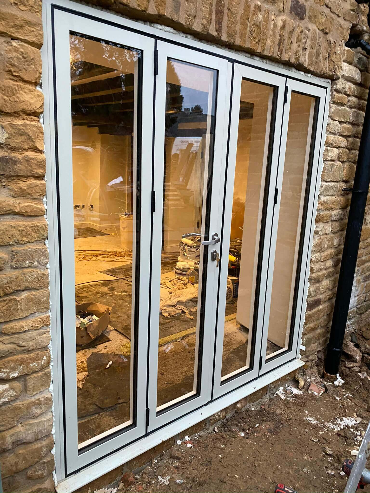 White patio doors installed in old brick wall