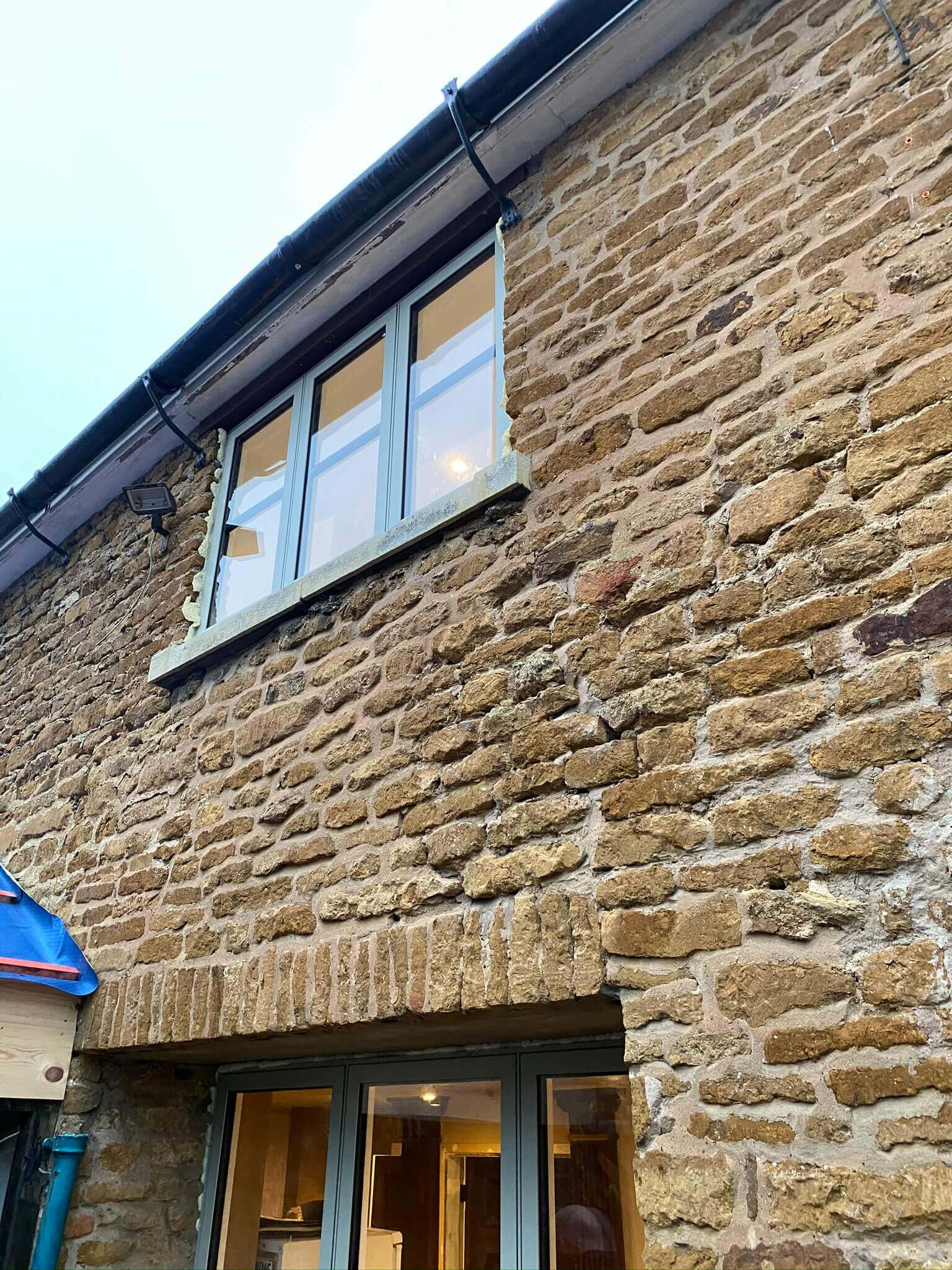 Old brick wall with new windows and patio doors
