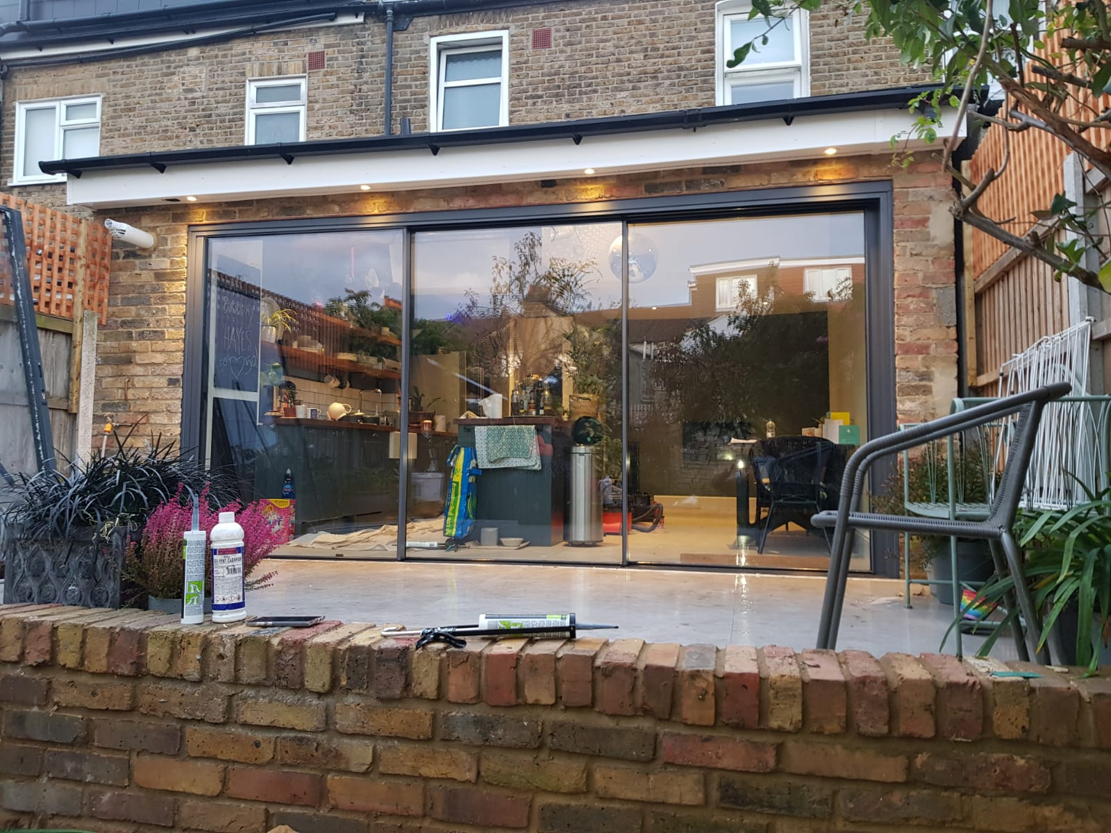 house extension with large patio doors plants and outdoor chair