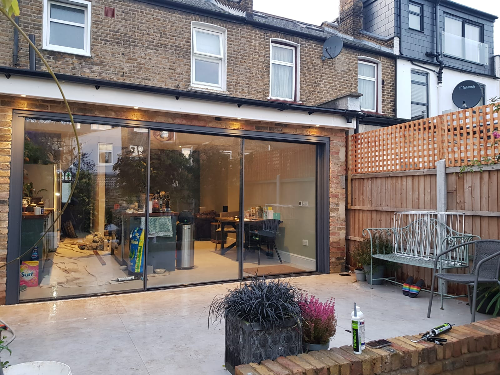 house extension with large patio doors plants and outdoor chairs