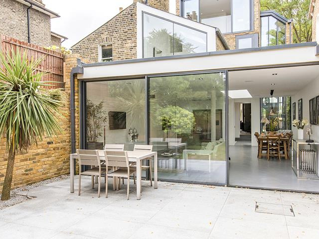 open sliding doors to patio with palm tree and outdoor furniture