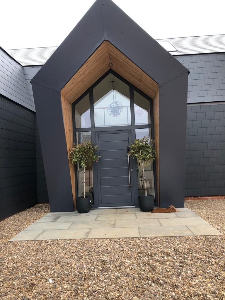 grey front entrance door with trees in planters and gravel drive