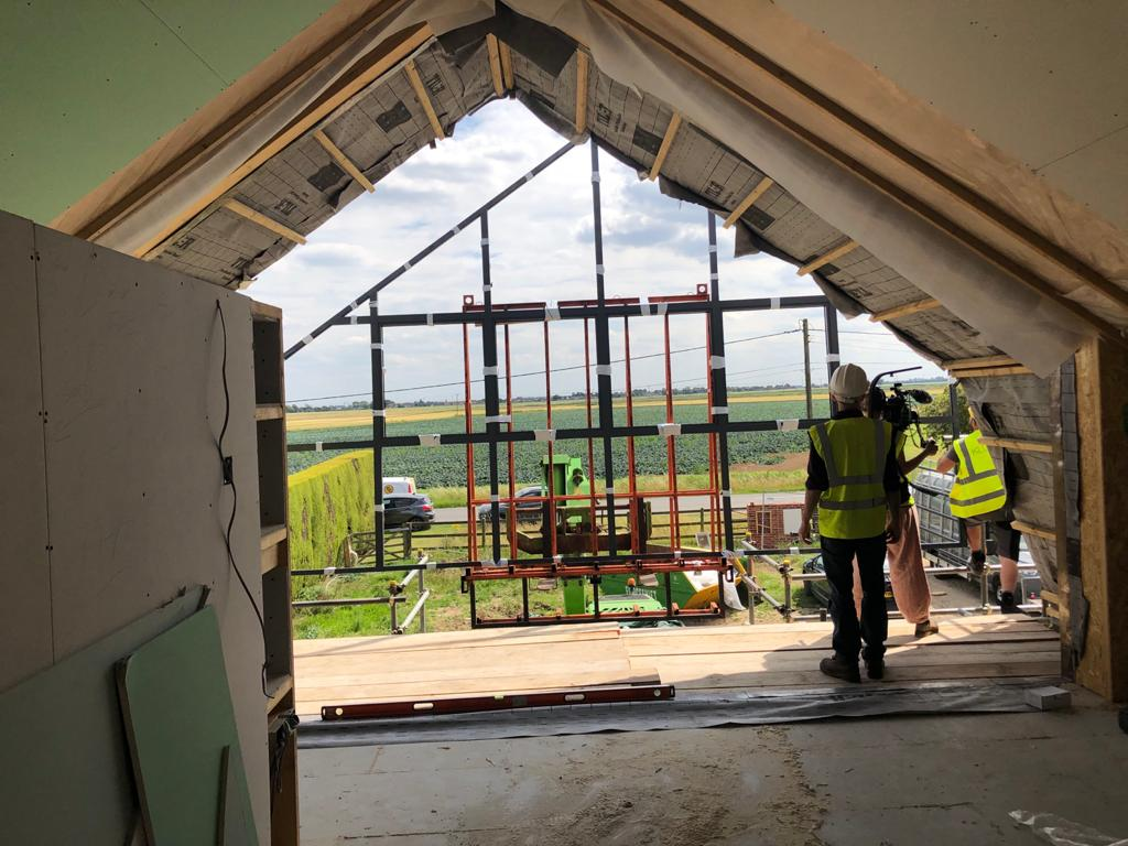 Internal view of window installation with green fields in background