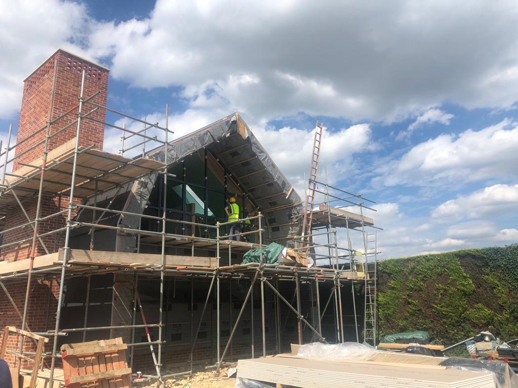 window fitter on scaffold at new build Dutch barn